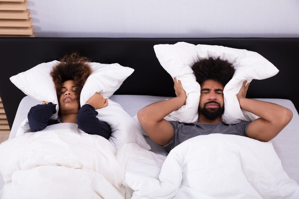 Young Couple Covering Their Ears With Pillow