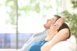 man and woman relax on white sofa with their arms behind heir heads