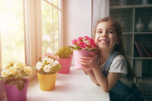 cute child girl puts flowers in pots on the window.