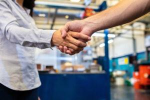 Colleagues shaking hands in factory shoo floor